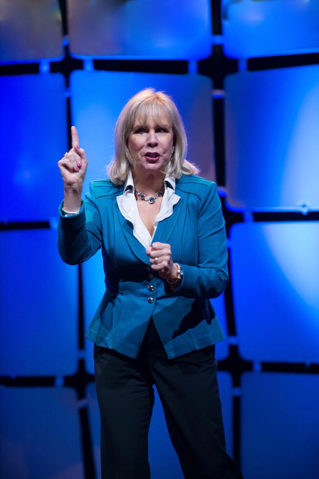 Motivational Speaker Linda Larsen on Stage Making a Point High Resolution