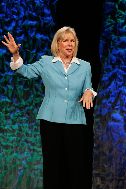 Motivational Speaker Linda Larsen on Stage Telling a Story